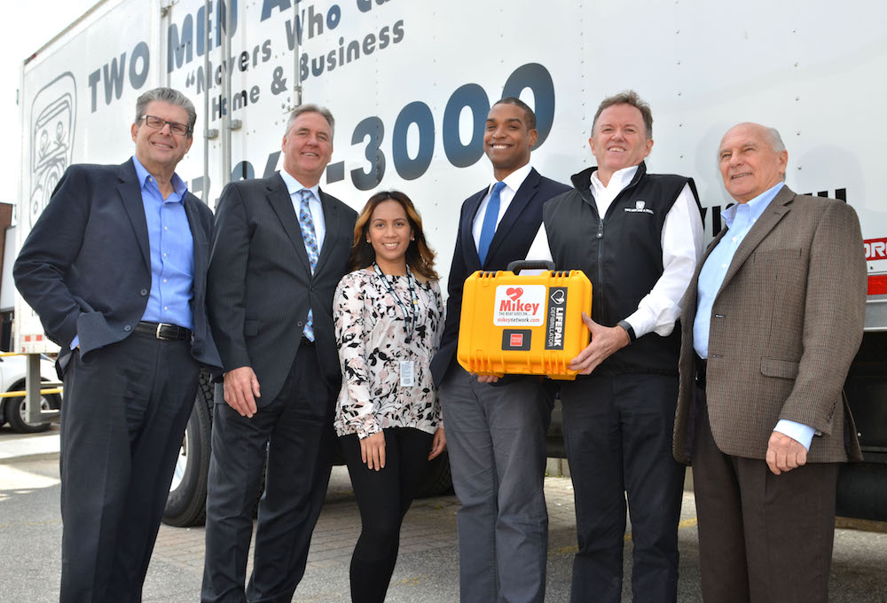 Every TWO MEN AND A TRUCK® moving vehicle in Canada sports a Mikey defibrillator with drivers and movers trained to use them. Toronto East franchise Owner Paul Bolté  (holding the defibrillator) takes pride in supporting The Mikey Network, the company's charity of choice. Photo: Nicola Betts