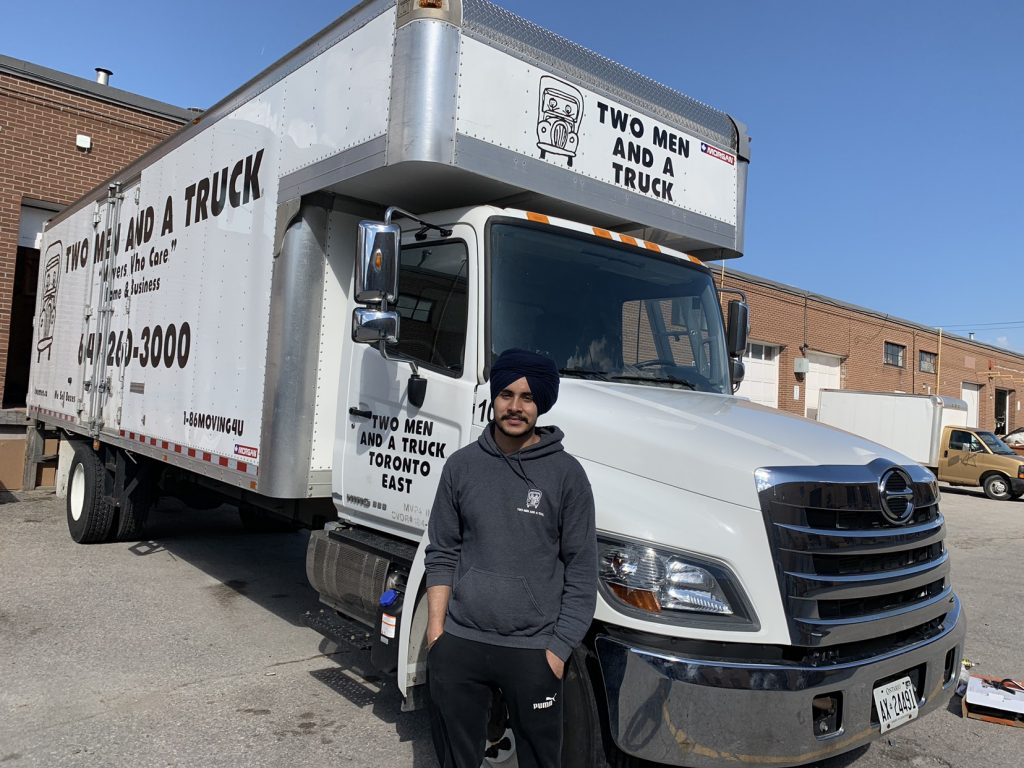 Iqbal Singh in-front of a company truck