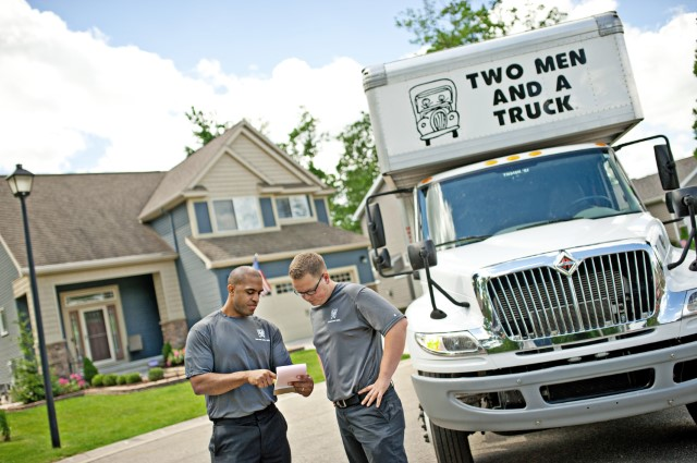 Two men and a truck movers reviewing a quote