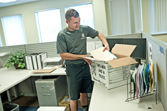 Two Men and a truck employee packing office goods in to a box
