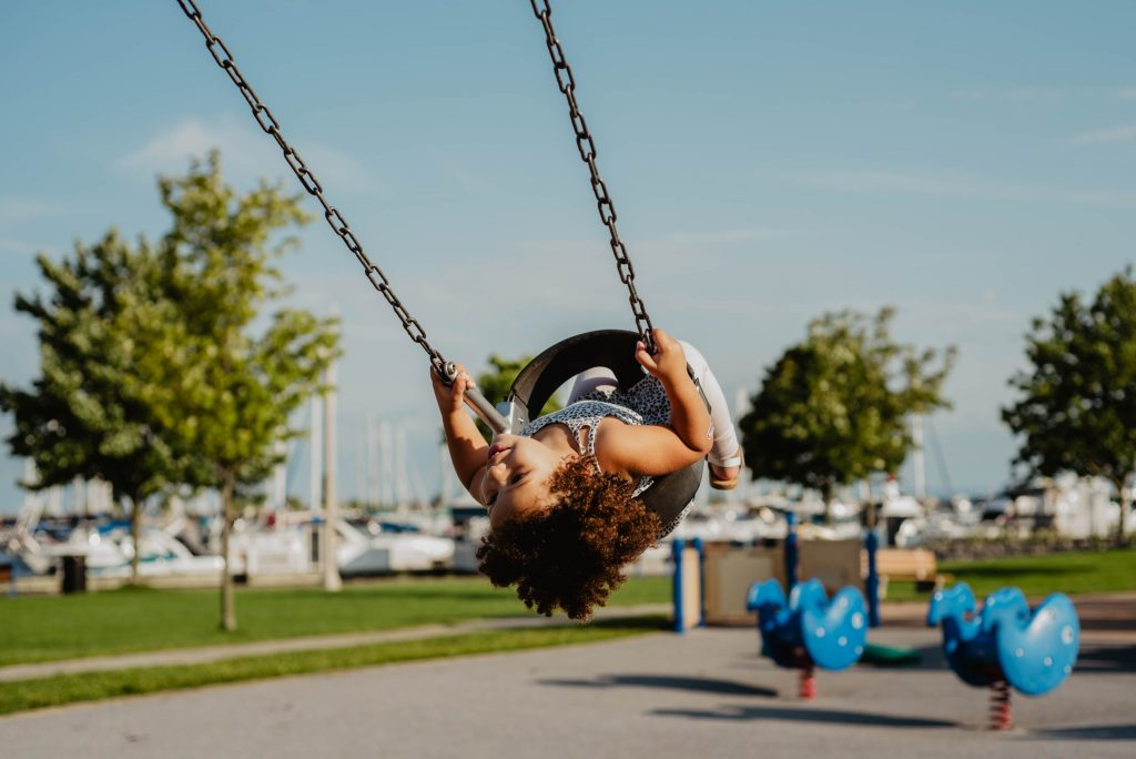 Oakville, Ontario Canada.   Child swinging by a marina