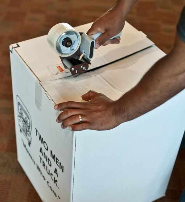sealing moving box with tape gun